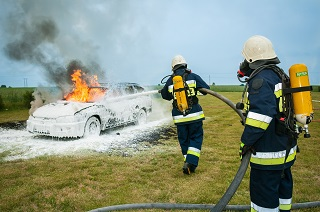 image of car fire being extinguished by fire fighters