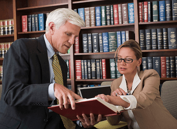 Man and a woman reviewing a book together in an office