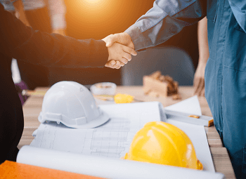 Two people shaking hands over a table that has blueprints and hard hats on it